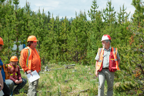 2 men in PPE looking at each other in a forest