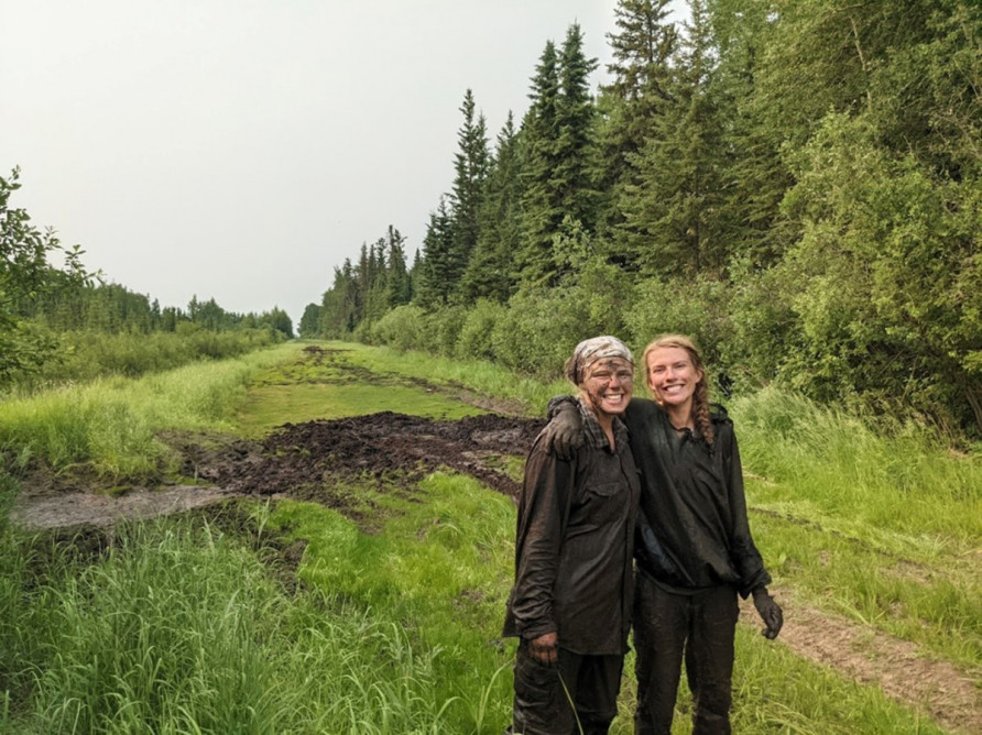 2 field technicians covered in mud, on a grassy road in the Chinchaga
