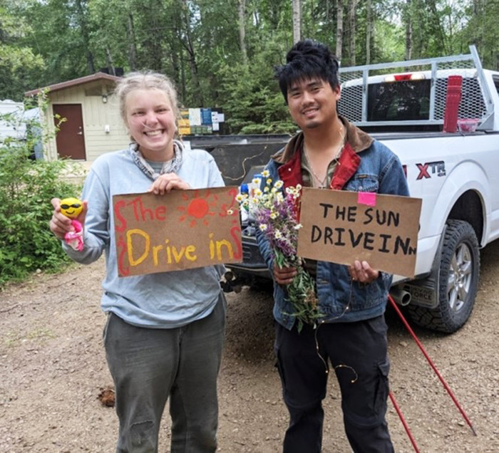 Janine and Christian with cardboard signs that say The Sun Drive In.