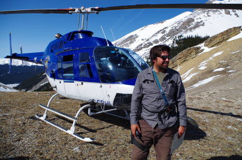 Terry Larsen, on a mountain, in front of a helicopter.