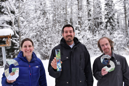 3 GIS employees stand outside in the winter holding wooden block letters spelling GIS