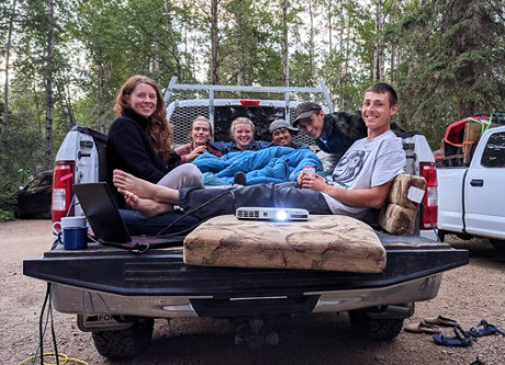Field techs sitting in the bed of a pickup truck with cushions and sleeping bags, using a laptop and projector to watch a movie